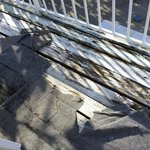 some sort of torn and ugly outdoor rug covering up the unkept deck