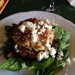 Crab cake on portobello  mushroom with grilled tomato, on a bed of spinach with a balsamic reduc