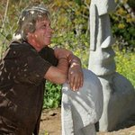 Environmental Artist Bryan Morse leans of one of his Easter Island sculptures
