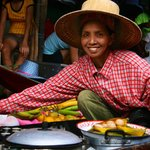 Thai lady sells fresh cooked food snacks to tourists from her boat at Damnoen Saduak Floating Ma