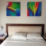 Fresh, modern feel to the room with art over the headboard