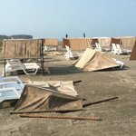 High winds blow over the shades on beach at Occidental, Cartagena, Colombia - beach almost deser
