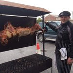 Rudi the owner with the pig on a spit