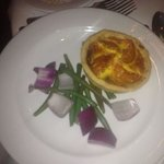 goats cheese flan with chunks of onion and cold greenbeans