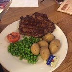 Ribeye steak cooked medium well with new potatoes and peas