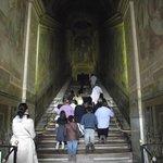 Católicos rezando e subindo a Escada Santa de joelho