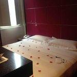 Camera con petali di rosa sul letto