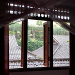 A rainy view from our bed, framed by mosquito netting and wooden shutters. Room #2.