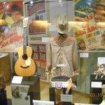 Gene Autrey display of boots, guitar, shirt, hat, belt, & posters.