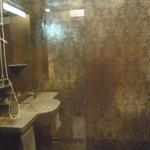 Small shower glass does let water splash around from rain shower, interesting tiles