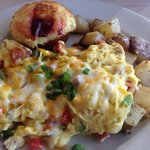 Skillet omelet with bell peppers, sausage, ham, cheese, and onions with seasoned potatoes and a