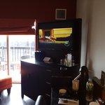 Coin salon avec sur la droite tv écran plat et bureau avec cafetière