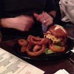 Bacon cheeseburger on a pretzel bun with onion rings