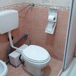 cramped toilet set up. Broken toilet paper dispenser.