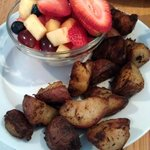 Sides of Home Fries and Fresh Fruit.