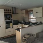 Kitchen with microwave, washing machine, dishwasher, oven, hob...