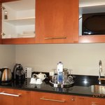 The kitchenette with microwave, fridge, utensils, plates, glasses & an espresso machine.