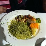 Salmon fillet with pesto pasta and vegetables.