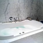 Large jet bath surrounded by heated marble flooring
