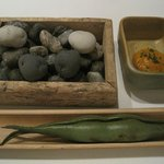 Appetizer - little potatoes on a bed on little stones, some sort of pod, and dipping sauce.