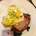 Potato cakes topped with poached eggs and hollandaise sauce, with a side of bacon and wilted spi