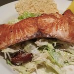 Caesar salad topped with salmon