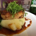 Pork belly on top of mash potato with a side of kale