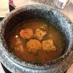 Fantastic tom yum soup with prawns and pork, served in a large granite pot.