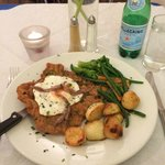 Veal Scallopina Holstain, topped with a fried egg and served with roasted potatoes and vegetable