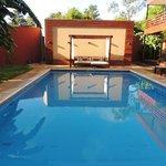 hermosa piscina con sillones confortables y espacios verdes