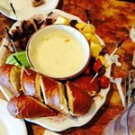 Swiss cheese fondue with potatoes sausage apple and pretzel bread