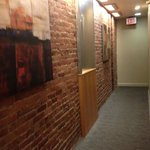 Cool exposed brick  and metal /wood decor in narrow hallway