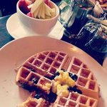 Blueberry and Lemon Curd waffle with dish of fresh fruit.