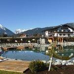 Blick von der Gartensauna mit Schwimmteich zum Hotel