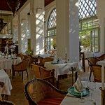 Salle de restaurant et sa terrasse dérrière les baies vitrées