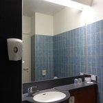 La salle de bain ; le lavabo avec un grand miroir au dessus