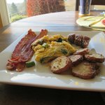 Grace's homemade breakfast - fresh veggie omelet, bacon, potatoes, a basket of bread and butter,