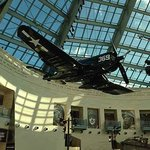 A USMC Corsair fighter from WW2 hangs on display under the glass spire of the entry hall.