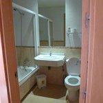 vista del baño con bañera y mampara. El espejo estaba roto