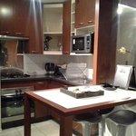 Cozinha simples, porém funcional. Possui panelas, talheres, tacas, copos, etc.