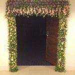 Вход в конф. зал, украшенный к празднику живыми цветами.