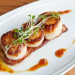 Pan-seared sea scallops with pork belly and maple sherry glaze