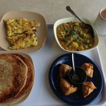 Clockwise from top left- Omelette with chilli, Potato curry, singaras and chutney, and parathas.