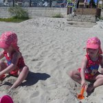 Twins, happily playing in the beautiful sand