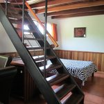 Hotel room with bed and staircase to loft