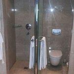 Banheiro e chuveiros separados por uma parede de mármore. Total exclusividade.