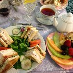 """A turkey bacon club with salad, the """"Cream Tea"""" and a personal pot of tea."""