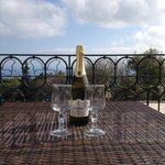 Some fizz on our hotel balcony with sea and pool view.