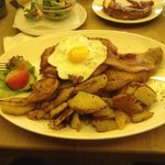 Schnitzel with bacon and an egg and potatoes