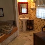 Attached bathroom with antique wood vanity table, counter space & large tub